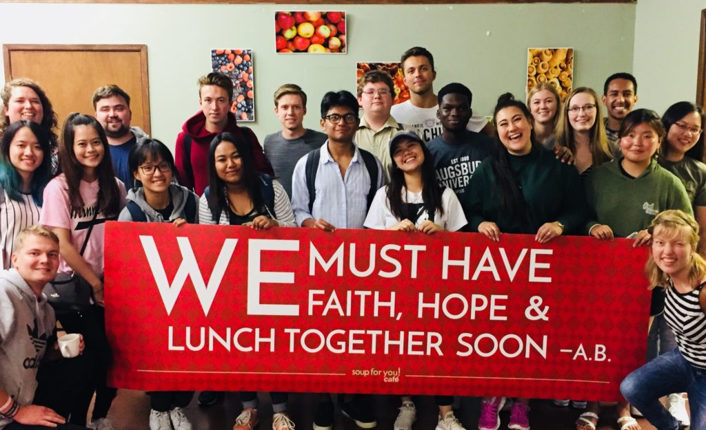 People holding a banner that reads We must have faith, hope and lunch together soon - A.B.